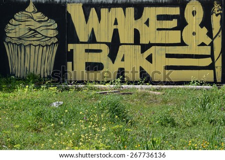 ATHENS, GREECE - APRIL 6, 2015: Cupcake and cannabis rolled cigarette graffiti with wake and bake slogan slang for smoking marijuana for breakfast. - stock photo