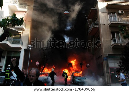 ATHENS-GREECE - APRIL 26. Fire fighters tries to extinguish burning cars following an arson attack by anarchists at a central police station in Athens, April 26, 2007.