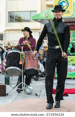 ATHENS, GREECE - APRIL 22, 2007: Two street artists, in a square of Athens, near Plaka, perform in front of a crowd that has gathered around them, in order to gain some money at the end of their show.