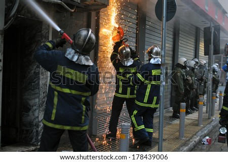 "ATHENS-GREECE - DEC. 20. Fire fighters, protected by riot police, tries to extinguish burning store named ""plaisio"" following an arson attack during mass riots in central Athens, December 20, 2008. - stock photo"