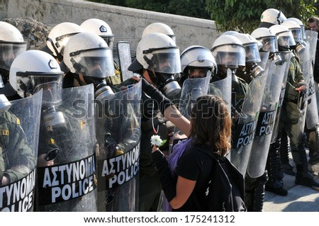 ATHENS, GREECE-DEC. 09, 2008. Young girl offering flowers to the riot police during demonstration, in front of Greek parliament, in Athens, December 09, 2008. - stock photo