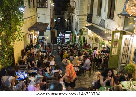 ATHENS,GREECE - JUL 21 : The touristic season  opened and tourists  visiting the famous Plaka area under Acropolis, July 21, 2013 in Athens,Greece