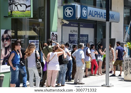 ATHENS, GREECE - JULY 1, 2015: Long line of people waiting to withdraw cash money from ATM cashpoint outside a closed bank. Capital controls during greek financial crisis. - stock photo
