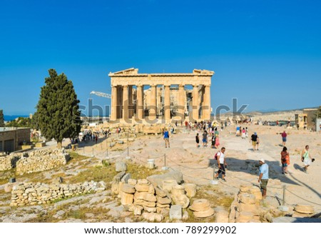 Athens, Greece - July 16, 2017: Tourists near ancient greek temple Parthenon on Acropolis at sunset.