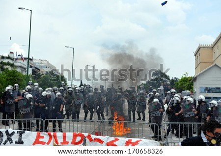 ATHENS, GREECE -JUNE15. A molotov explodes next to riot police at the Greek Parliament during demonstration , in Athens, June 15, 2011. - stock photo