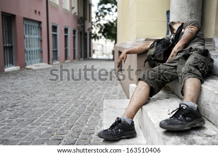 ATHENS, GREECE - JUNE 6: Man addicted to drugs lies on a doorstep in a narrow street of the center of Athens on June 6, 2010 - stock photo