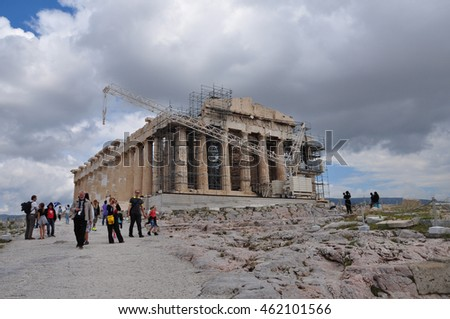 ATHENS, GREECE - MAY 6, 2014: People visiting the Acropolis and the temple of Parthenon under repairs with crane and scaffold.