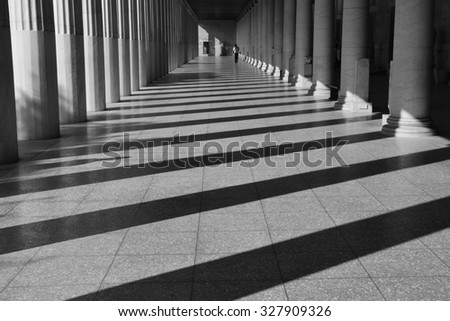 ATHENS, GREECE - OCTOBER 14, 2015: Man walking among the columns of stoa attalos at the ancient agora. Light and shadow abstract architecture black and white.