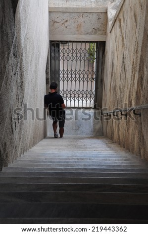 ATHENS, GREECE - SEPTEMBER 2, 2014: Man standing on marble stairs in stoa of attalos at the ancient agora.