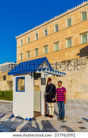 ATHENS - NOVEMBER 6, 2015: Tourist poses to the photo with the guard at the Tomb of the Unknown Soldier. The guard is held by The Evezones, a ceremonial unit of The Presidential Guard.