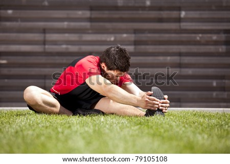 Athlete at the park warming and stretching - stock photo
