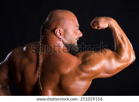 Athlete bodybuilder  demonstrating muscles of the back and arms on a dark background