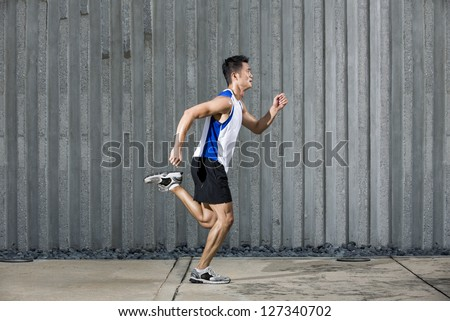 Athlete Chinese man running in urban city. Asian Runner jogging outdoors with a wall in background. Male fitness concept. - stock photo