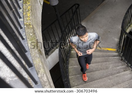 Athlete Chinese man running outdoors in urban city. Asian running man, listening to music on smart phone while running up stairs. Sporty Male fitness concept.   - stock photo