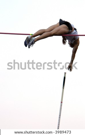 Athlete clearing the bar during a pole vault event in Prague, Czech Republic. - stock photo