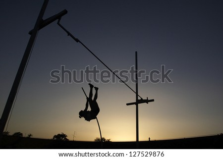 Athlete compete in pole vault during sunset - stock photo