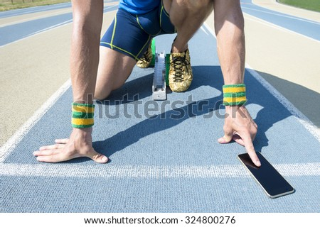 Athlete crouching at the starting line of a running track wearing Brazil colors wristbands checking his mobile phone