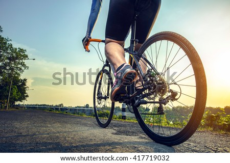 Athlete cycling on the road in the afternoon. - stock photo