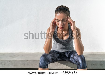 Athlete fitness running woman with headache migraine pain during cardio workout run. Asian athlete with health problem feeling exhausted during difficult strength training exercise at gym. - stock photo