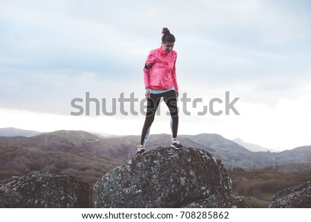 Athlete girl trains in the mountains. Sport tight clothes. Intentional motion blur.