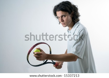 Athlete holding a tennis racket and ball and looking at the camera.  Horizontally framed shot. - stock photo