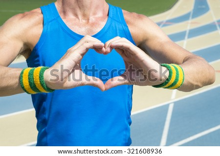 Athlete in Brazil colored wristbands holding up heart hands at the running track - stock photo