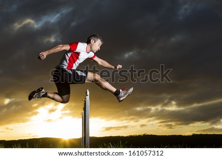athlete in hurdling in track and field in sunrise - stock photo