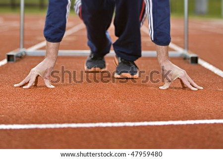 Athlete in sprint position on a running track - stock photo