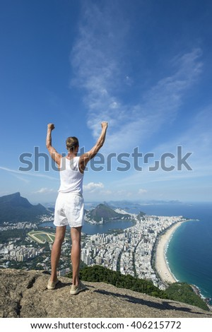 Athlete in vintage white uniform stands with arms punching the air in celebration at an overlook view of the Rio de Janeiro Brazil skyline - stock photo