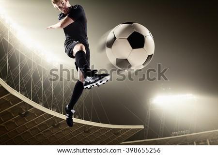 Athlete kicking soccer ball in stadium - stock photo