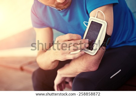 athlete listening music and touching armband for smartphone (intentional sun glare) - stock photo