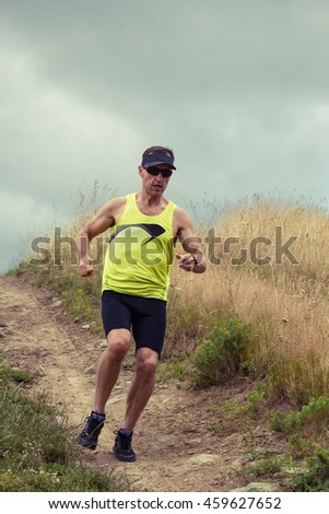Athlete male runner running downhill on dirt road