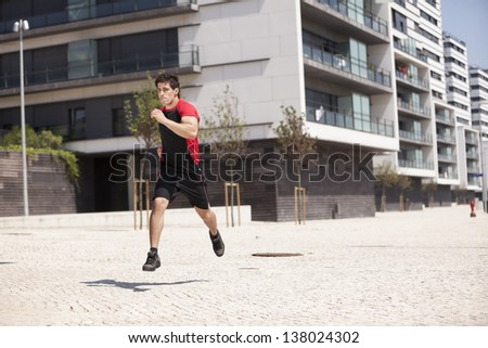 athlete male running at the city park - stock photo
