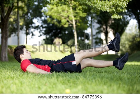 Athlete man at the city park making some abdominal - stock photo
