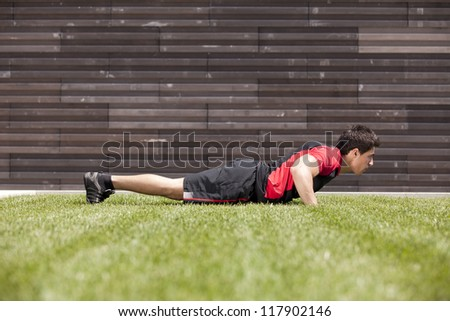 Athlete man at the city park making some push up - stock photo