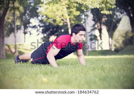 Athlete man at the city park making some push-up - stock photo