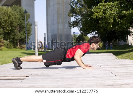Athlete man at the city park making some push ups - stock photo