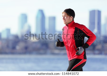Athlete man running sport. Runner in winter jogging outdoors with city skyline in background. Male fitness model in Montreal, Canada. - stock photo