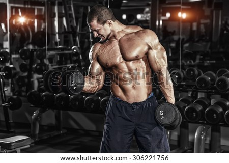 Athlete muscular bodybuilder in the gym training biceps with dumbbell - stock photo