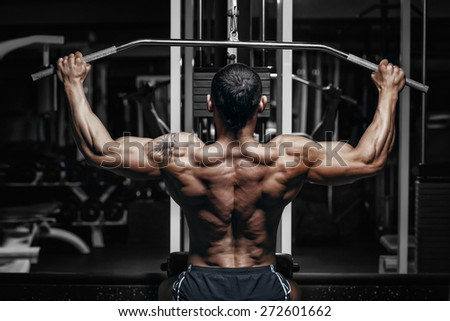 Athlete muscular bodybuilder training back on simulator in the gym - stock photo