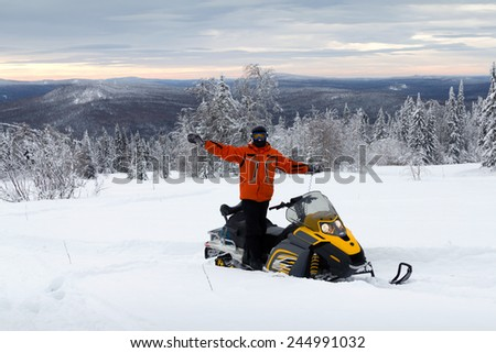 Athlete on a snowmobile in deep snowdrifts mountains of the Southern Urals. - stock photo