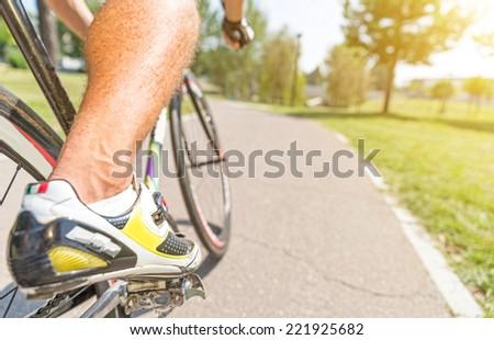 athlete on his bicycle. close up on the shoes while he is turning - stock photo