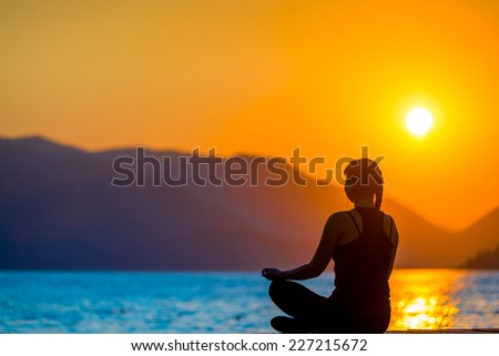 athlete on the background of mountains and rising sun relaxes - stock photo