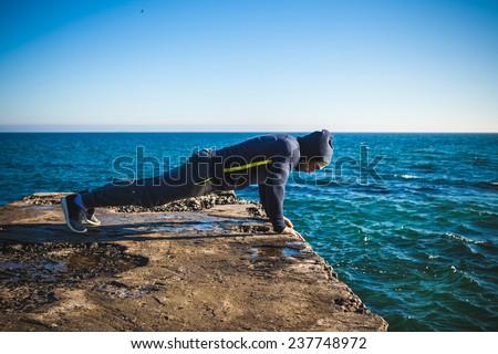 Athlete performing exercises on beach - stock photo