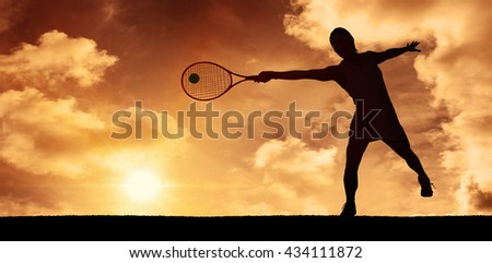 Athlete playing tennis with a racket against a beautiful sunset