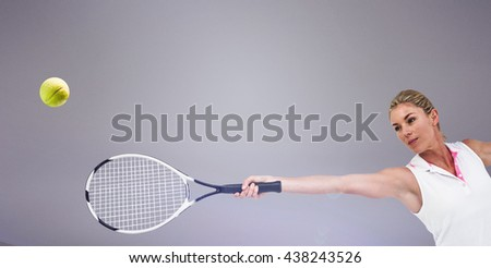 Athlete playing tennis with a racket against grey background - stock photo