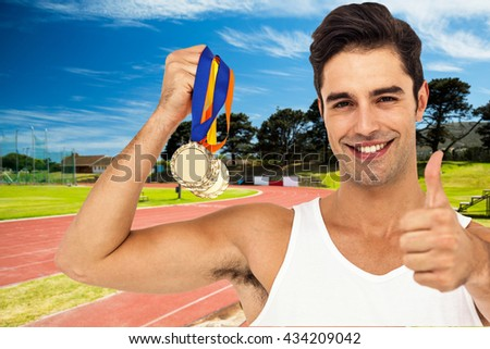 Athlete posing with gold medals against high angle view of track - stock photo