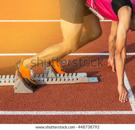 athlete ready on the starting blocks in stadium - stock photo