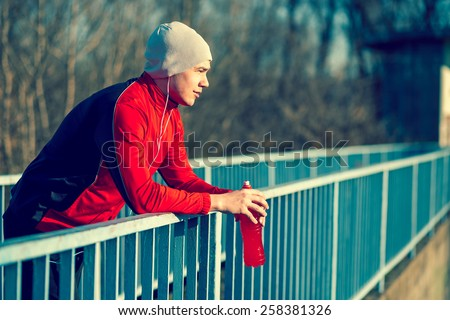 Athlete relaxing after an intense workout, holding a bottle of an energy drink - stock photo