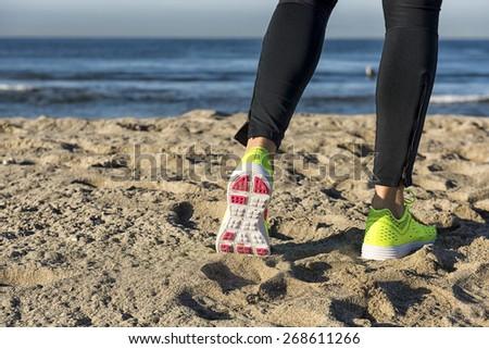 Athlete runner feet on the beach  - stock photo